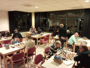 Een gezellige speelzaal vol met schaakleden